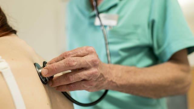 Ein Arzt hört mit einem Stethoskop den Rücken einer Patientin ab