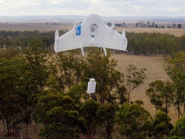 Drohne steht senkrecht in der Luft und seilt Paket ab.