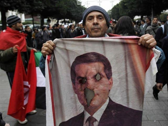 Protestierender mit einer Fahne mit dem Gesicht von Zine el-Abidine Ben Ali, Augen und Mund sind ausgestochen.