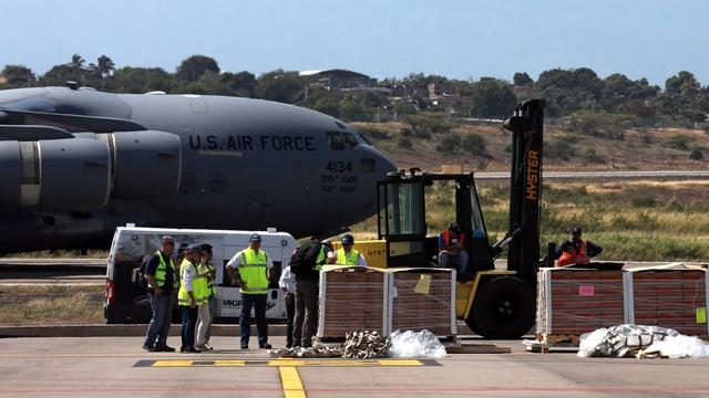 Flugzeug der US-Army mit Kisten im Vordergrund