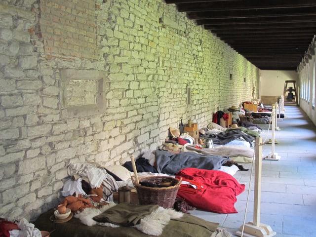 Ein mittelalterlicher Kreuzgang, darin ein Lager aus Strohmatten.