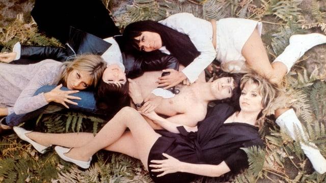 Eine Gruppe von Frauen liegen auf einem nackten Mann.