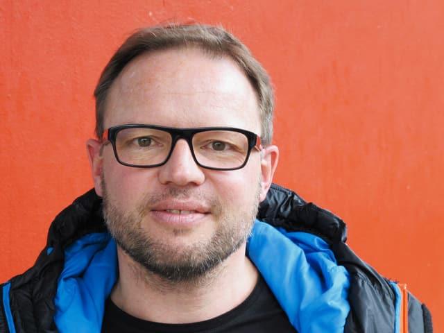 Mann mit blauer Kapuze und Brille vor rotem Hintergrund.