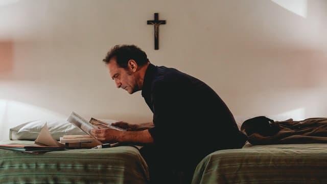 Ein Mann sitzt auf einem Bett und liest in einem Buch.