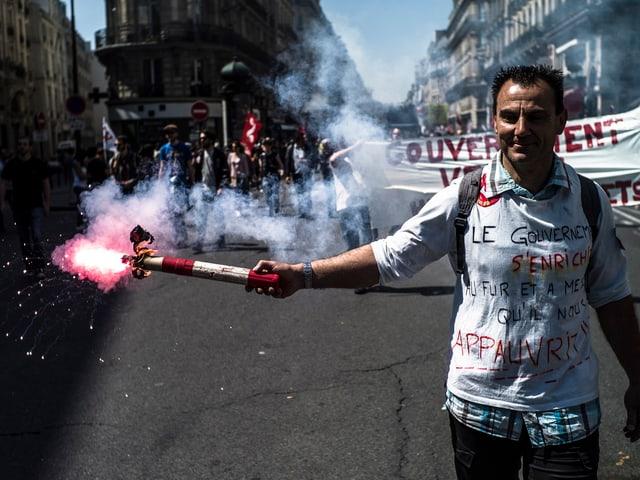 Ein Mann hält eine Fackel während einer Demonstration in Paris.