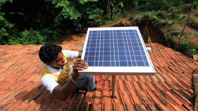 Ein Mann montiert ein Solarpanel auf ein Dach