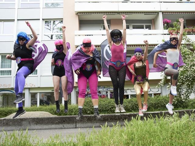 Eine Gruppe Mädchen in Superheldinnen-Kostümen springt in die Luft.