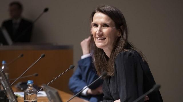 Frau lächelnd an Pult im belgischen Parlament.