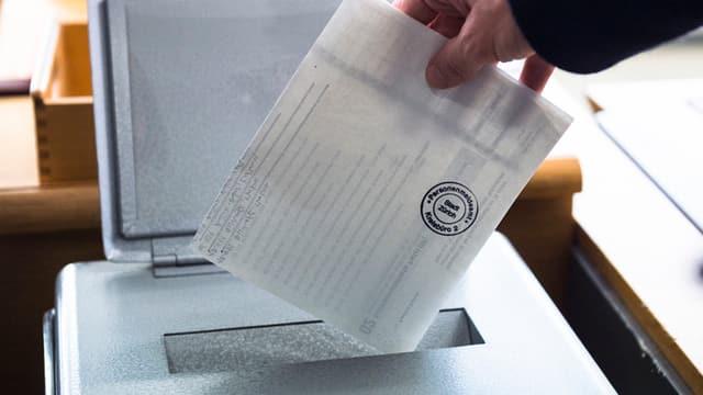 Eine Person wirft einen Wahlzettel ein.
