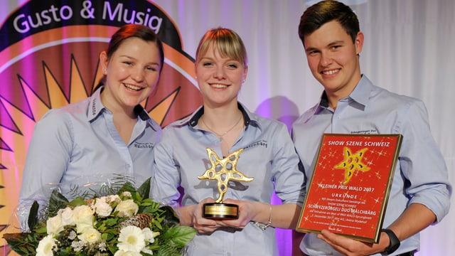 Zwei junge Frauen und ein junger Mann mit Auszeichnung und Diplom.