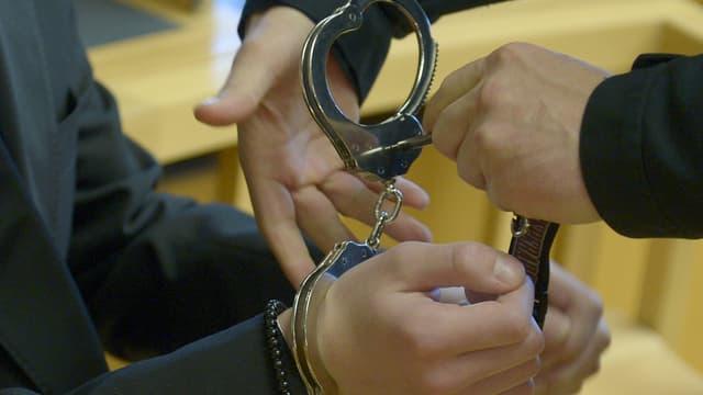Einem jungen Mann werden Handschellen angelegt (Symbolbild)