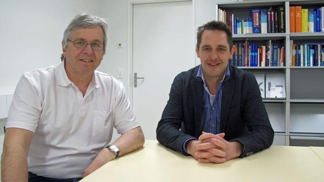Rainer Klöti und Ralf Bucher an einem Bürotisch.