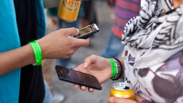 Zwei Jugendliche halten an einem Festival ihre Handys in den Händen.