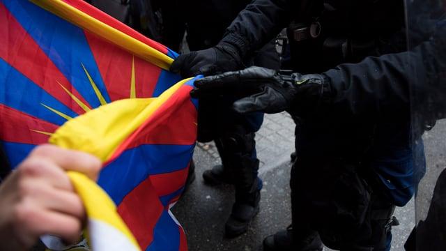 Polizist senkt eine Tibetfahne an einem Protest in Bern am 15. Januar 2017