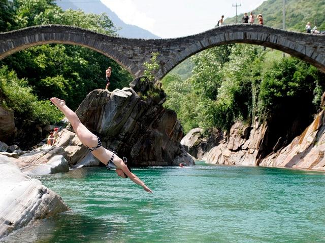 Eine Frau springt von einem Stein in die Verzasca.