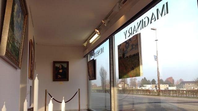 Bilder an den Wänden vor Schaufenster