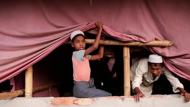 Zwei Rohingya-Kinder schauen unter einer Decke hinaus.