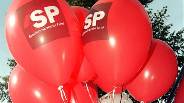 Ein paar rote Ballone mit der Aufschrift SP schweben in der Luft.