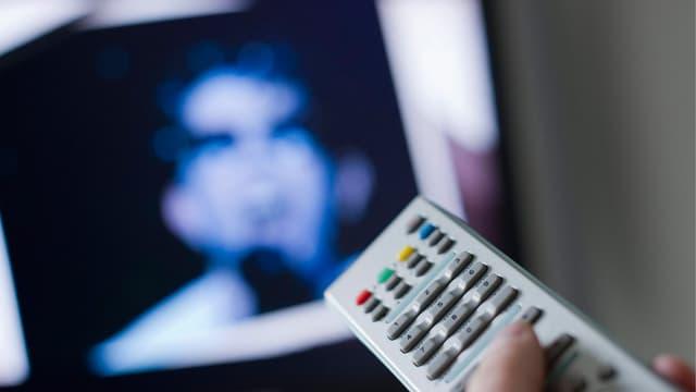 Im Vordergrund hält eine Hand die Fernbedienung eines Fernsehers in der Hand. Im Hintergrund ist verschwommen der Kopf eines Mannes auf der Mattscheibe zu erkennen.