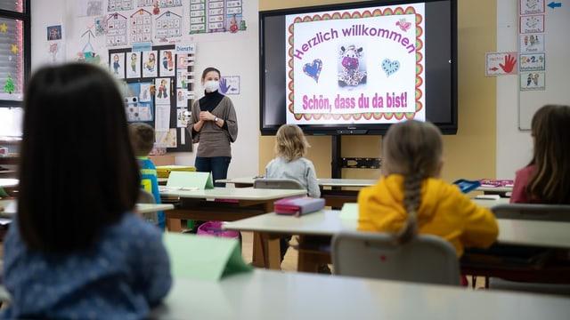 Scolasta en stanza da scola cun scolaras e scolars.