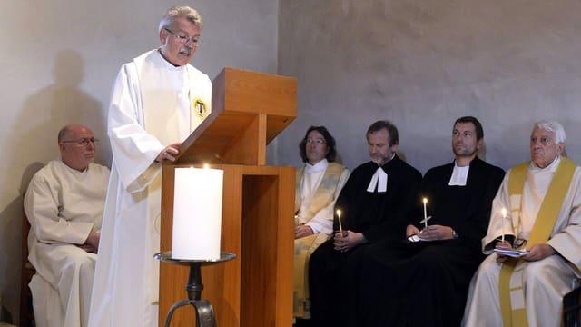 Ein Priester steht an einem Pult und liest etwas vor.