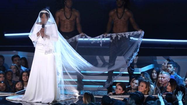 Eine Frau im weissen Brautkleid mit Schleppe.