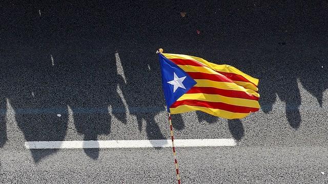 Menschenschatten hinter der Flagge Kataloniens