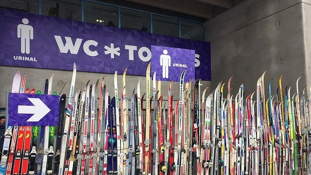 Purtret da skis davant tualetta publica.