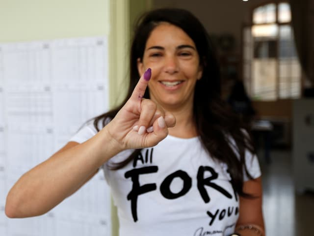 Eine Frau hebt den gekennzeichneten Finger, dass sie gewählt hat.
