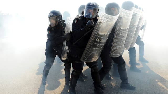Italienische Gendarmen mit Schutzschild und im schwarzen Gewand.