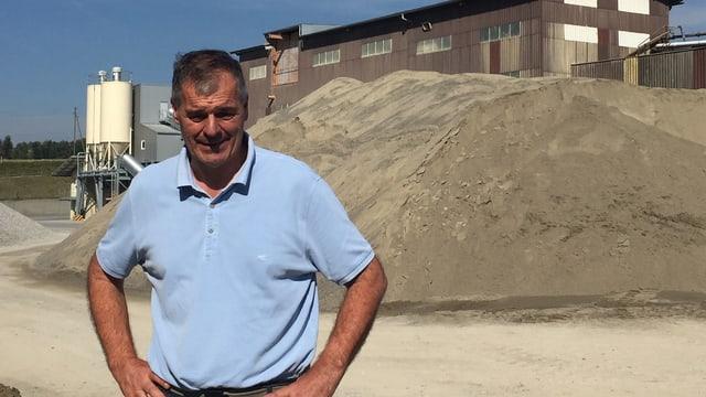 Mann vor Sandhaufen und Werksgebäude.