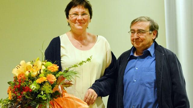 Dr. Mark Mäder bekommt einen Blumenstrauss überreicht.