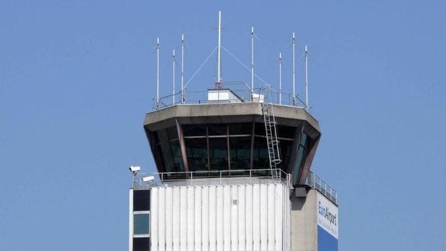 Der obere Teil des Kontrollturms von unten fotografiert, einige Antennen auf dem Dach, im Hintergrund der Himmel.