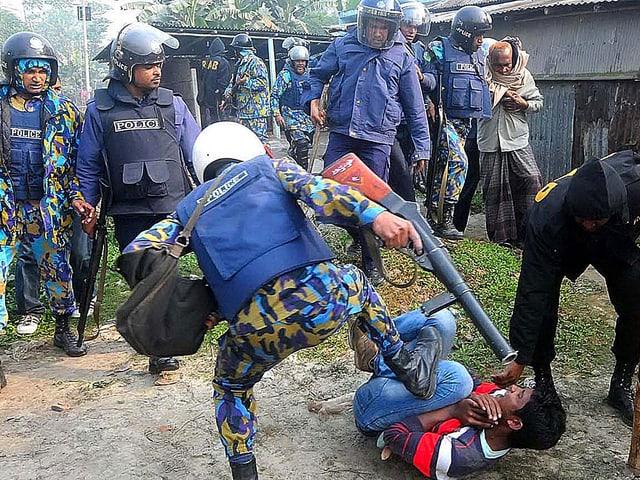 Polizisten verprügeln einen Demonstranten.
