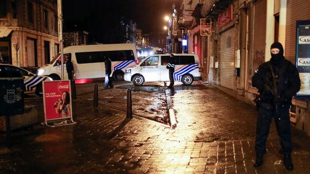 Polizeifahrzeuge und ein vermummter Beamter auf der schwach beleuchteten Strasse.