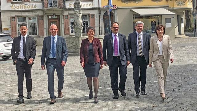 Eine Gruppe von sechs Politikern (zwei Frauen und vier Männer) gehen auf einem Platz.