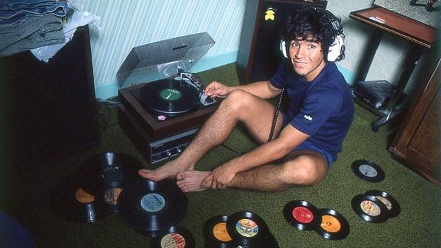 Ein junger Maradona sitzt auf dem Fussboden neben einem Plattenspieler. Um ihn herum sind viele Vinyl-Platten, er hat Kopfhörer auf.