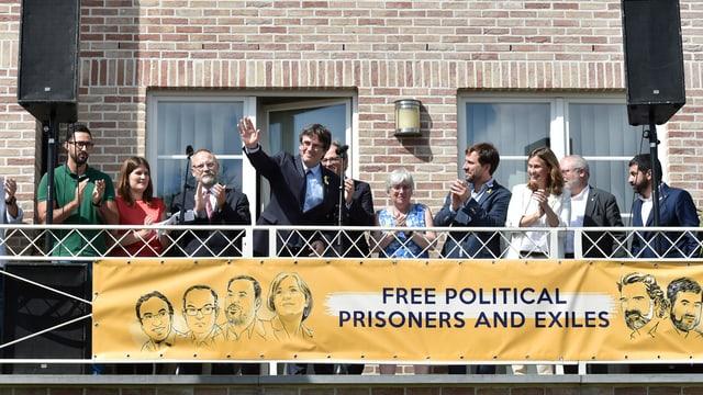 Leute auf einer Terrasse. Puigdemont grüsst mit erhobener Hand. Ein Plakat fordert die Freilassung aller politischer Gefangener und Exilanten.