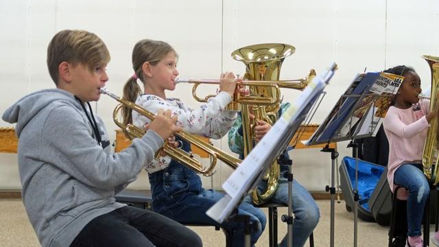 Drei Kinder spielen während des Musikunterrichtes auf Blasinstrumenten.