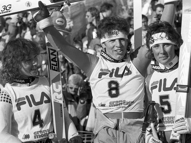 Schwarz-Weiss Fotografie mit den drei besten Riesenslalom-Fahrerinnen in Siegespose, im Renndress mit Startnummern und Skiern.
