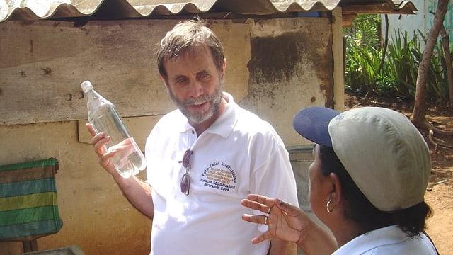 Martin Wegelin erklärt das Verfahren der Wasserdesinfektion mit der Pet-Flasche einer Frau in Peru.