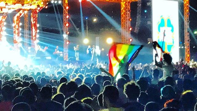 Konzertbesucher mit Regenbogenfahne