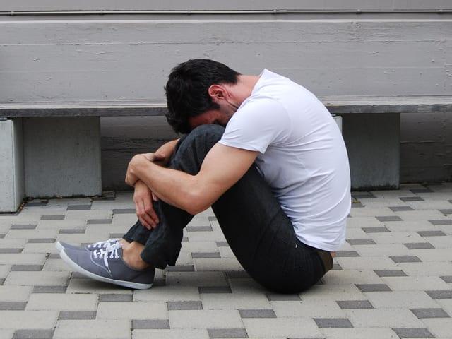Auf den Boden sitzen und die Beine anziehen.
