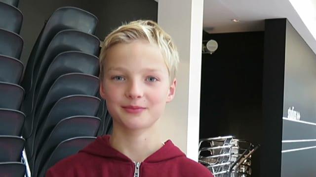 Ein blonder Junge mit rotem Pulli