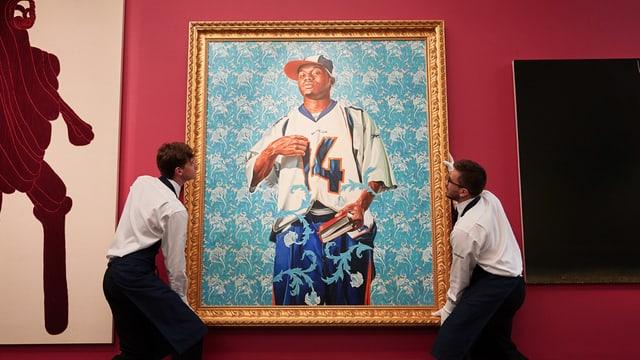 Ein gerahmtes Bild zeigt einen jungen schwarzen Mann in Hip-Hop-Kleidung und mit einem Buch in der Hand. Zwei Mitarbeiter eines Museums hängen es auf.