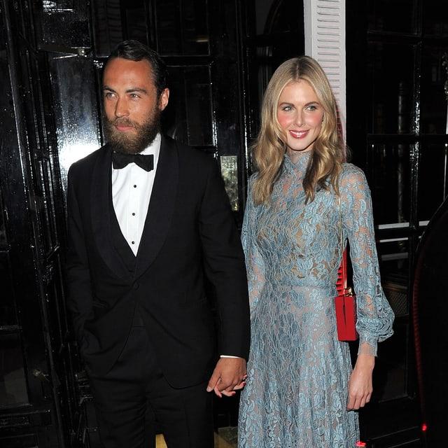 James Middleton mit einer blonden Frau im blauen Kleid an der Hand haltend.