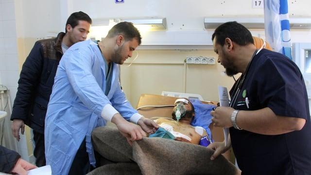 Ein verletzter in einem Spital, um ihn herum medizinisches Personal.