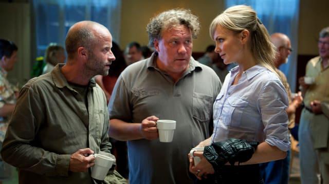 Zwei Männer und eine Frau stehen in einem Raum. Alle drei halten eine Kaffetasse in den Händen.