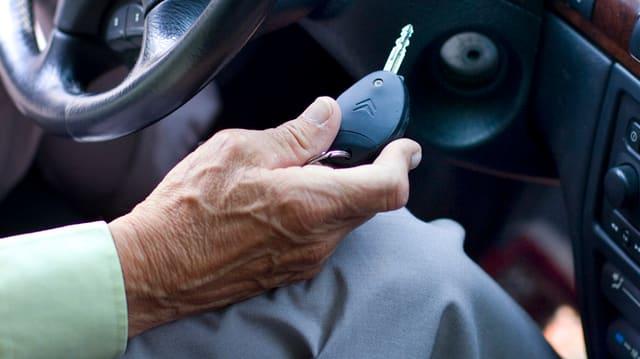 Greise Hand hält Autoschlüssel