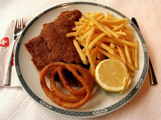 Ein Teller mit Schnitzel, Pommes frites und Zwiebelringen.